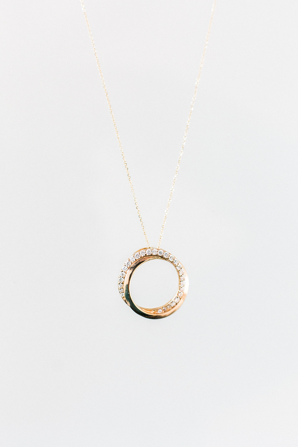 Image of gold diamond necklace in a circle shape.  Simple white background on a thin golden chain.