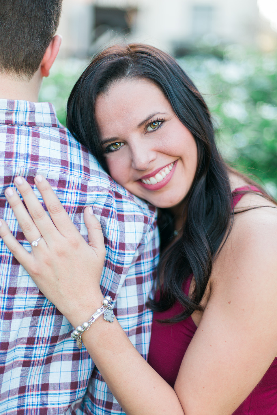 Image of an engaged couple in downtown Orlando, Florida.  She is smiling radiantly while cuddling into her fiance.