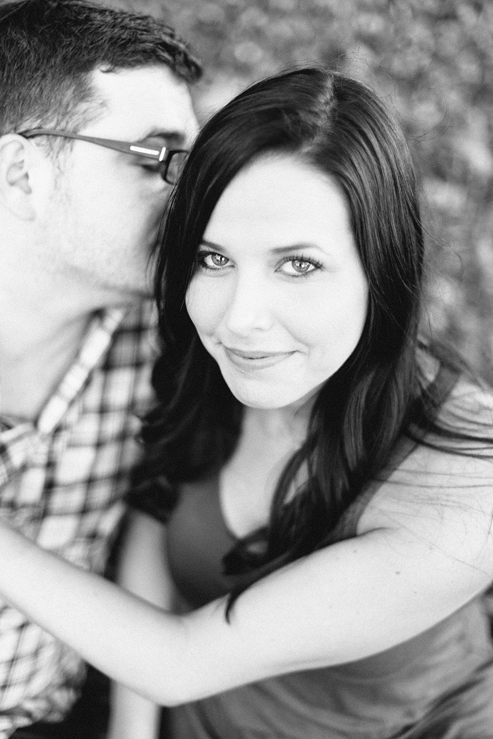 Picture of an engaged couple in downtown Orlando.  The woman is looking into the camera while holding her fiance.  The image is in black and white.