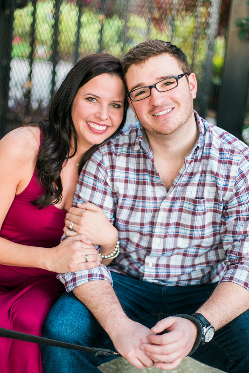 Picture of an engaged couple looking into the camera and smiling.  They are sitting in front of a gate on some steps in downtown Orlando, Florida
