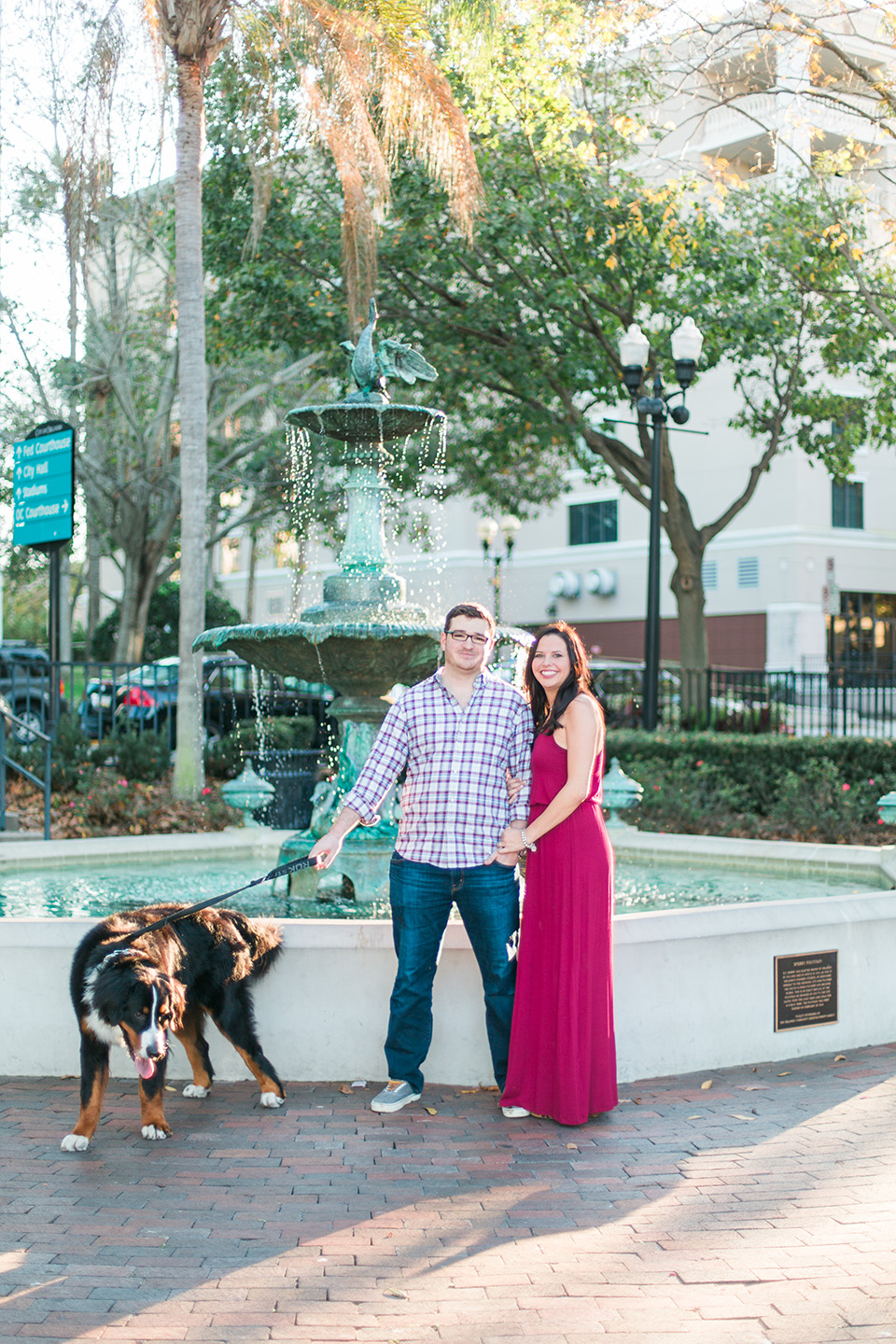 Picture of an engaged couple standing together in front of a fountain downtown Orlando with their Bernese Mountain Dog.