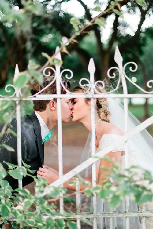 Image of a bride and groom kissing on their wedding day.  They are behind a white iron fence at the Rockin' H Ranch in Lakeland, Florida.