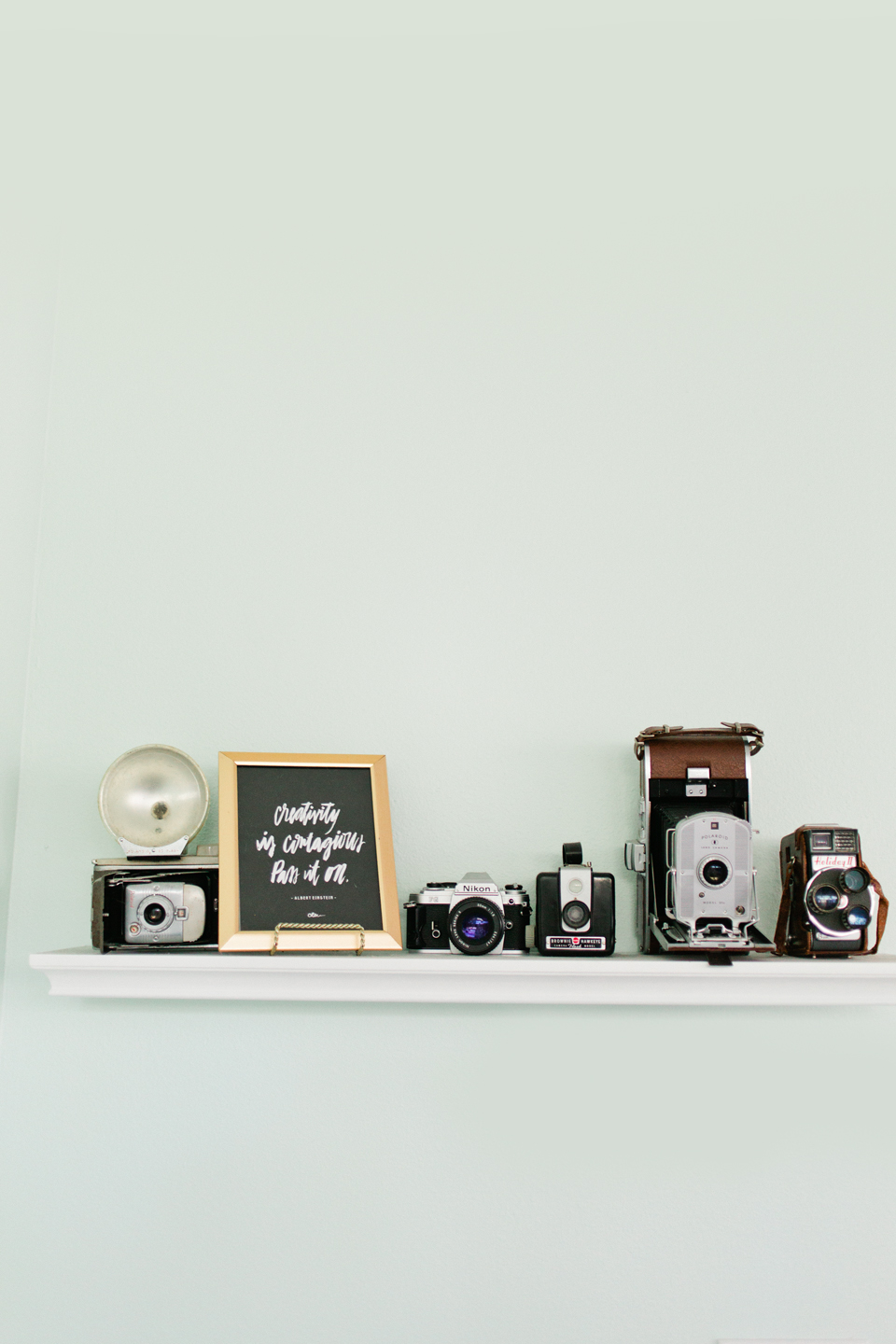 Picture of an office shelf with antique cameras lined up in a row.  The shelf is white and the wall is painted a light green.