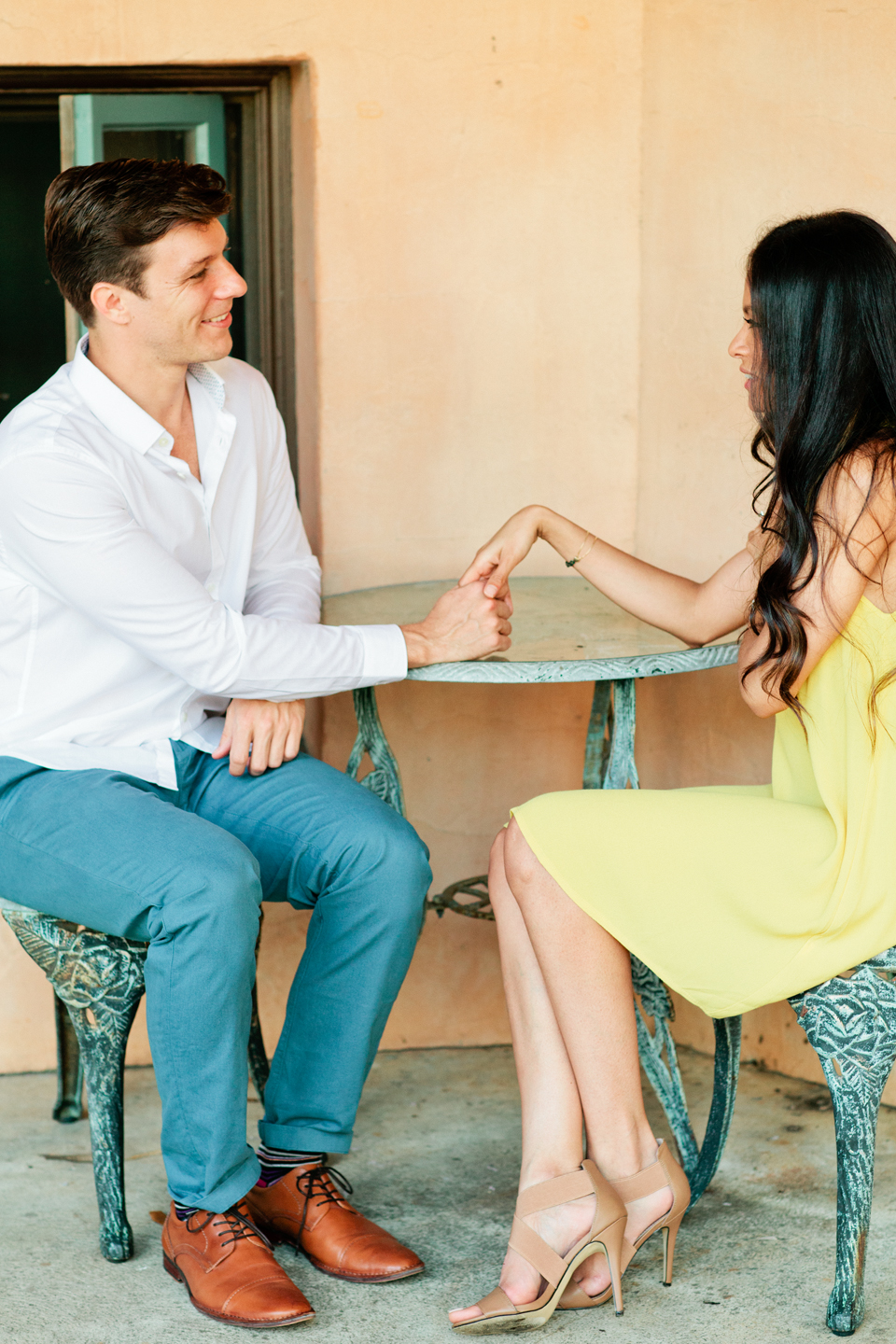 Picture of an engaged couple on a date.  They are sitting down together, facing each other, holding hands and smiling.