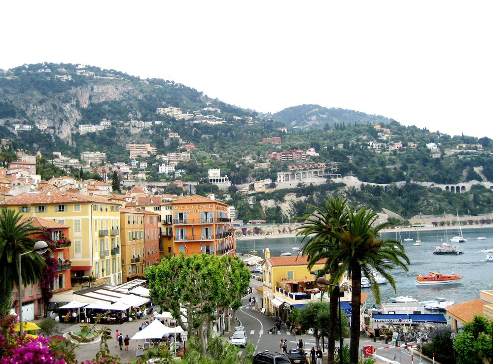 Image of a coastal city on the Mediterranean, in Villefranche Sur Mer.  There are tall palm trees and a port with mountains in the distance.