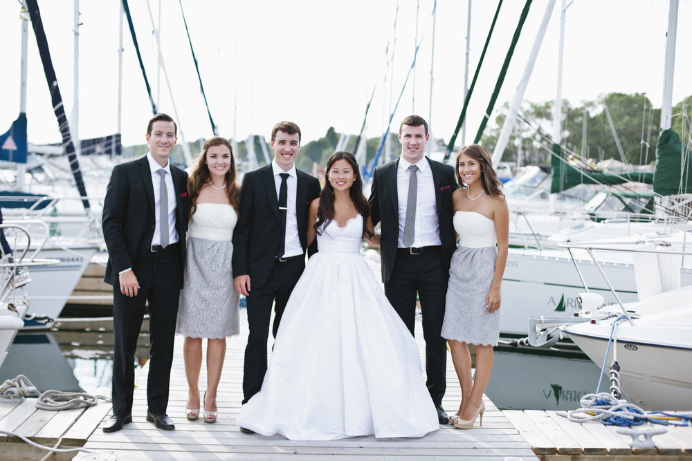 Picture of a bridal party on a wedding day, posing on a dock at a marina.  There are sailboats in the background.  There are two groomsmen, two bridesmaids, and a bride and a groom.