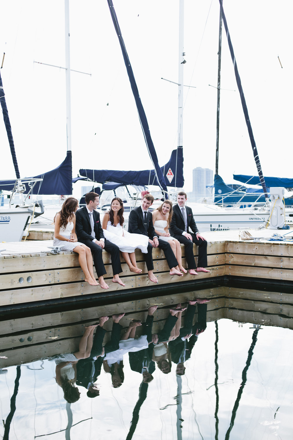 Picture of a bridal party sitting on a dock at a marina on a wedding day.