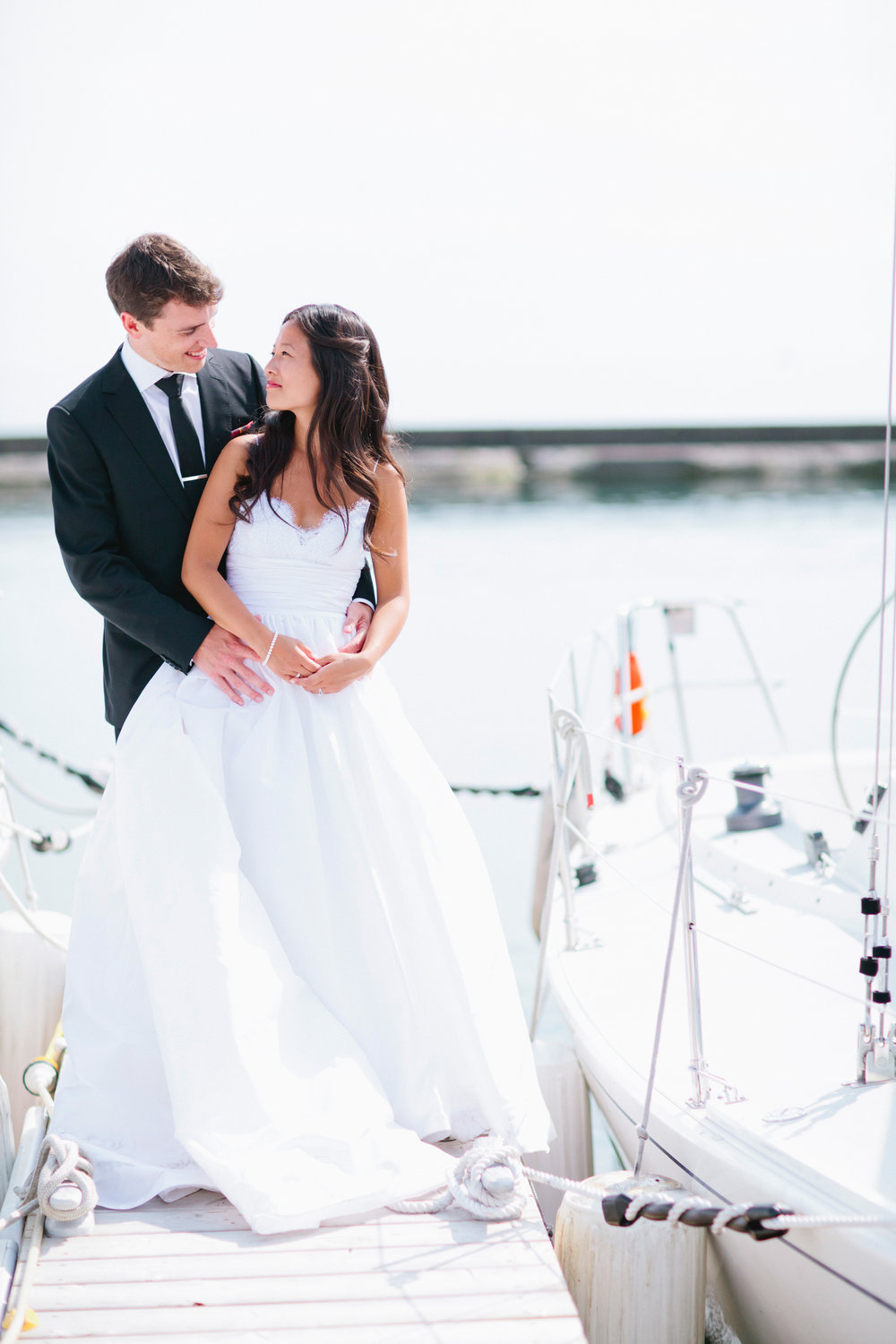 Image of a bride and groom on their wedding day.  They are on a dock at a marina, gazing at each other.  The bride has an Amsale gown.