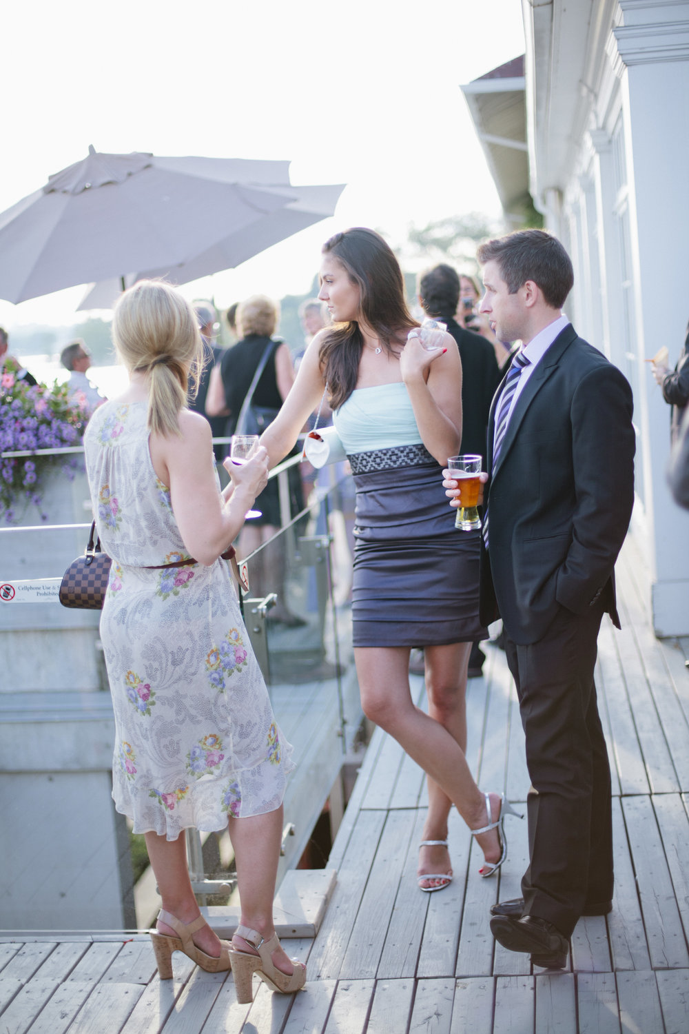 Image of a wedding day cocktail hour.  Guests are talking over cocktails and refreshments.