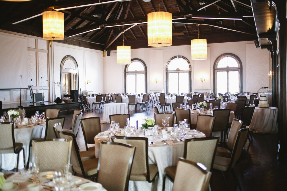 Picture of a reception at a yacht club.  There are large plush chairs and decorated tables.