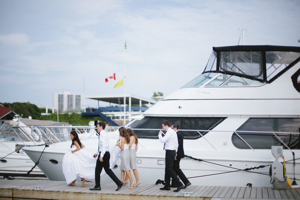 Image of a bridal party on a wedding day walking on the docks at a marina.