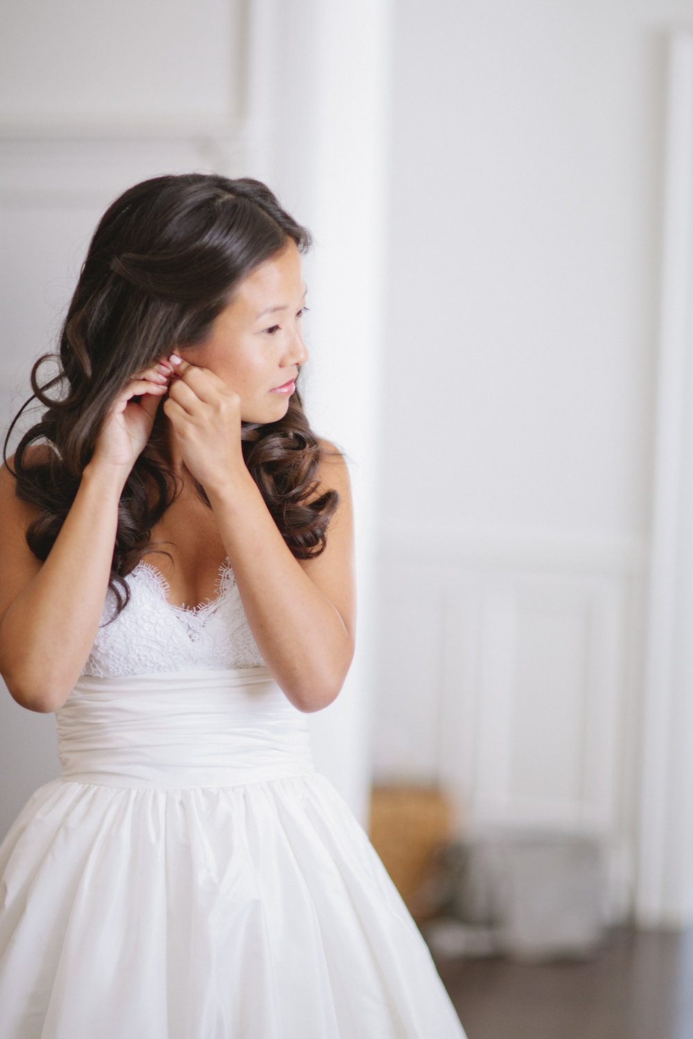 Picture of a bride getting ready on her wedding day.  She has long cascading curls and is putting on an earring.