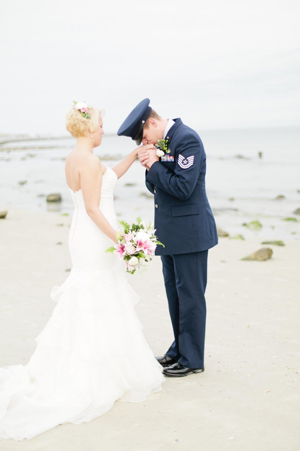 Image of a groom kissing the hand of his bride on the wedding day at the beach in Ponce Inlet, Florida  | Debra Eby Photography Co.