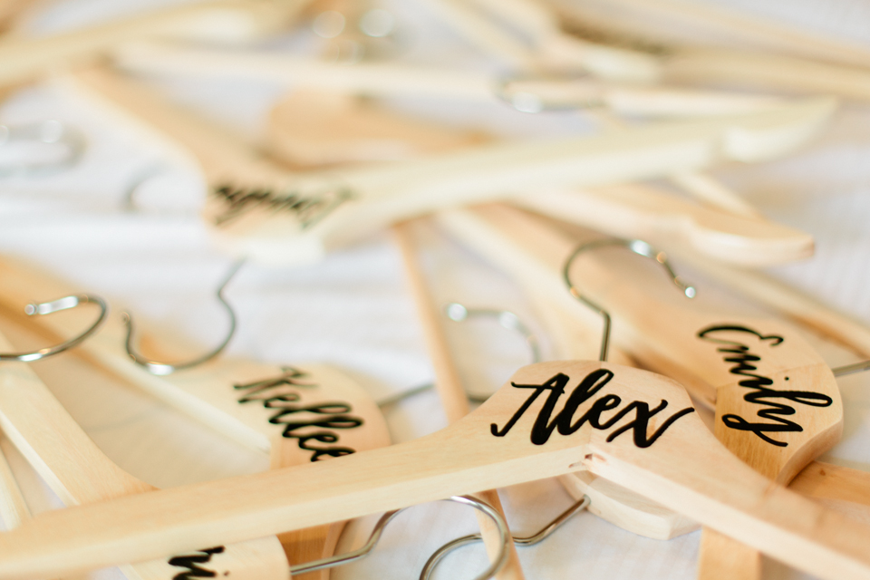 Image of hangers with hand lettering for the bridesmaids on a wedding day. | Debra Eby Photography Co.