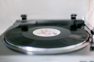 Picture of a record player.  The record is black and the record player is silver. | Debra Eby Photography Co.