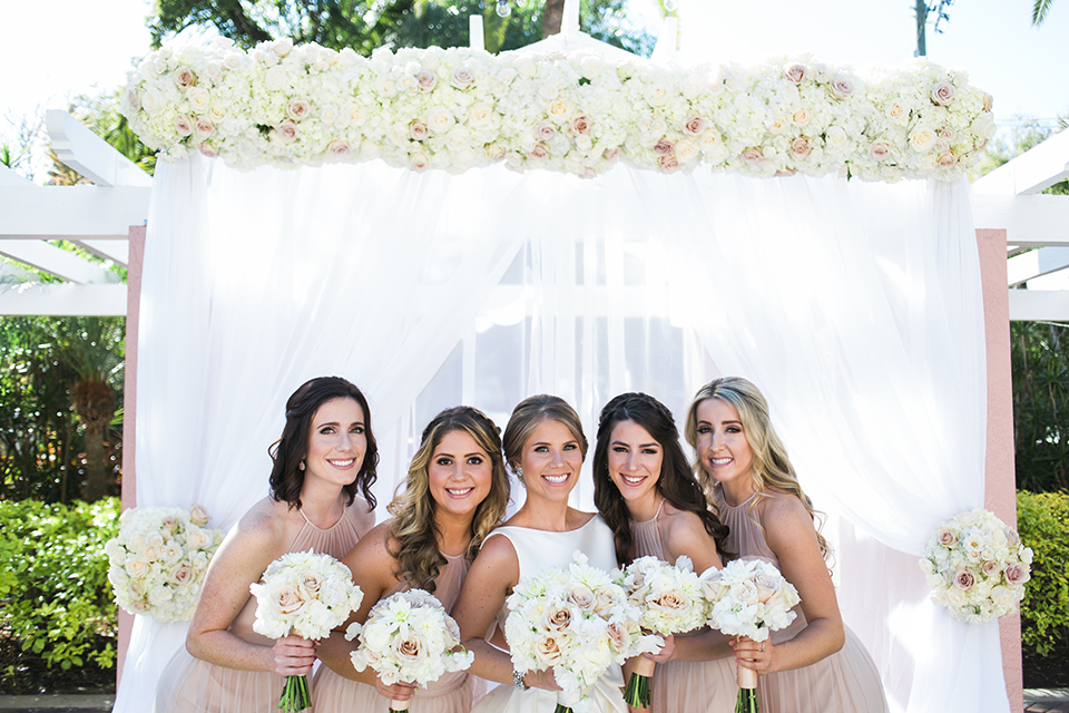 Bride with her bridesmaids and a floral canopy on a wedding day at The Vinoy in St. Pete, Florida | Debra Eby Photography Co.