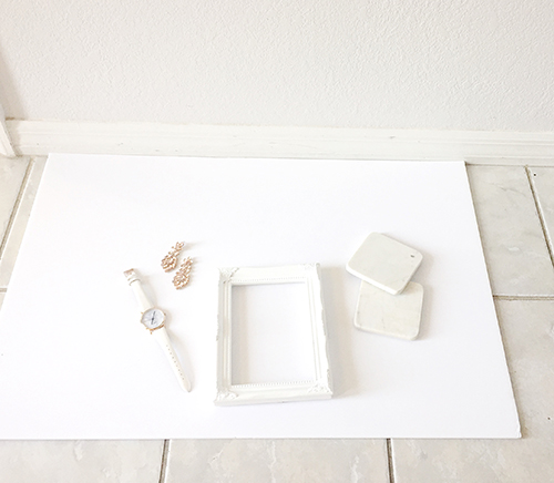 White posterboard is a cheap and easy solution for a backdrop.