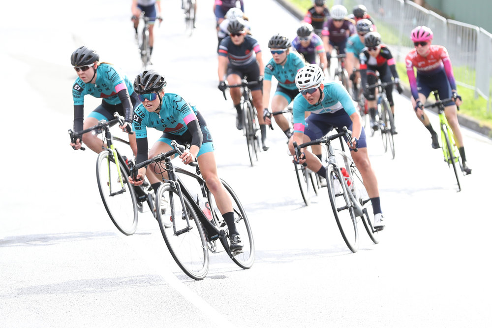 Kirsty, Lizzy, and Emma take the corner back onto the finish straight. Photo credit: Con Chronis Photography.