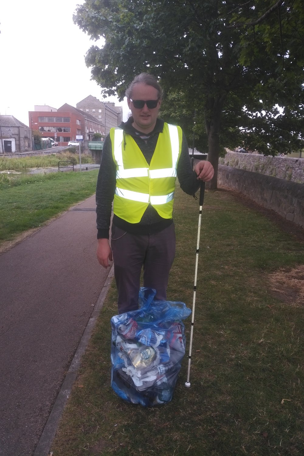 Declan Meenagh standing with a bag of rubbish next to the Royal Canal