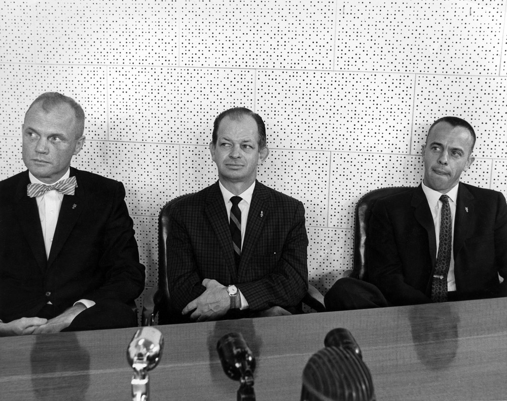"John ""Shorty"" Powers, the ""voice of the Astronauts,"" sits between John Glenn and Alan Shepard during a press conference interview with the first American in space (Shepard) and the first American to orbit the Earth (Glenn)."