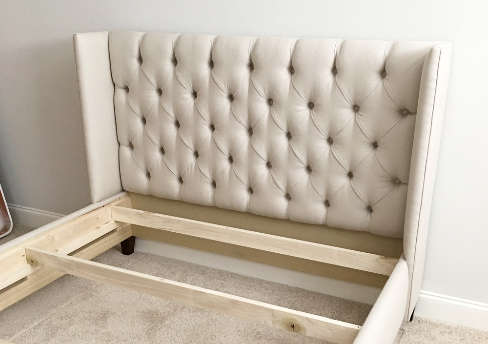 a custom queen winged headboard/bed being installed
