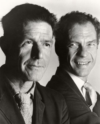 John Cage with Merce Cunningham slightly behind him, looking back and smiling at a serious Cage.
