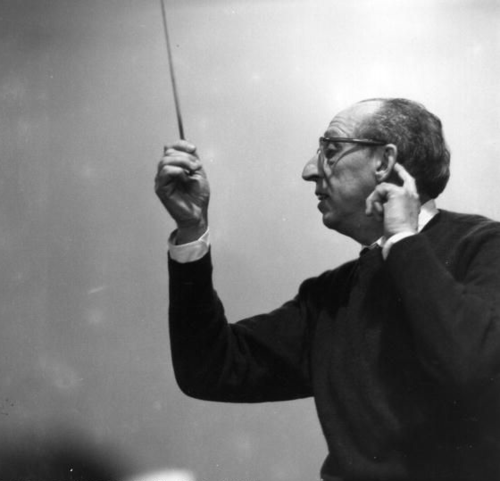 Aaron Copland listening to an orchestra, with his conducting baton raised.