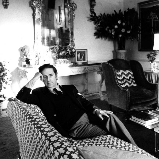 Menotti sitting on a couch with large graphic print in a very ornate room.