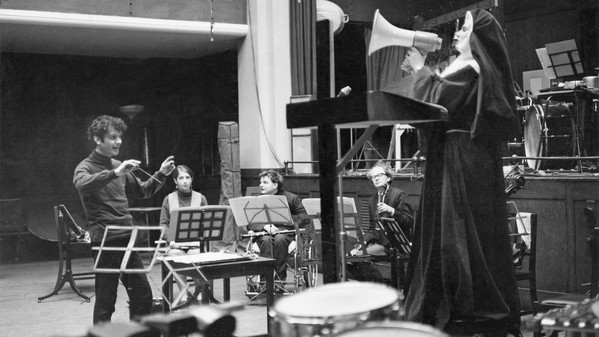 Peter Maxwell Davies in a small studio, conducting several instrumentalists and a nun with a blowhorn.