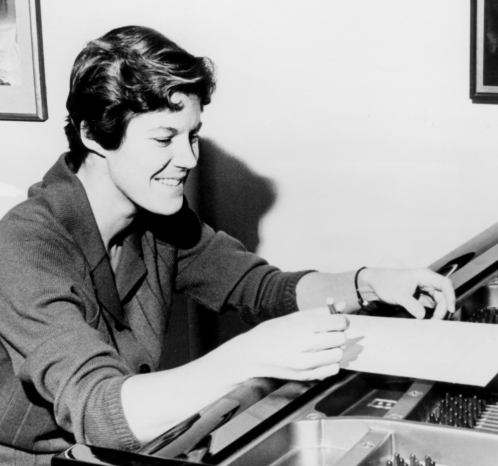 A casual photo of Ann Southam smiling over music she is writing overtop an open grand piano.