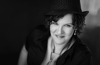 Catherine Laub in a fedora and tie with earrings, looking up at the camera and smiling.