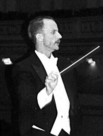 Tall, thin Dean Johnson in a tux conducting an orchestra.