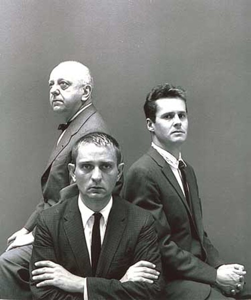 Three tiered gentlemen in suits with thin black ties - Flanagan facing forwards in front, with Ned Rorem and Virgil Thomson back to back behind him.