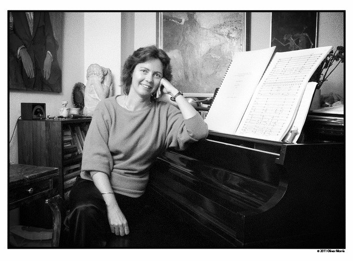 Zwilich in a baggy sweater with her elbow on a closed grand piano.