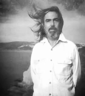 Robert Helps standing on a cliff over a body of water, salt and pepper beard and shoulder-length hair blowing in the wind.