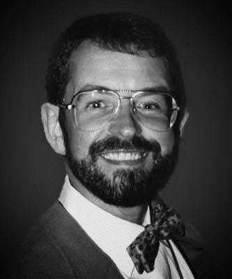 A smiling, beared DeLong with glasses and a bow tie.