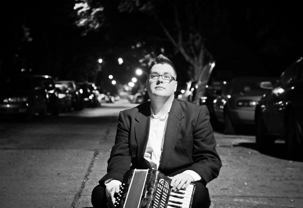 Michael Park sitting under a streetlight with his accordion.