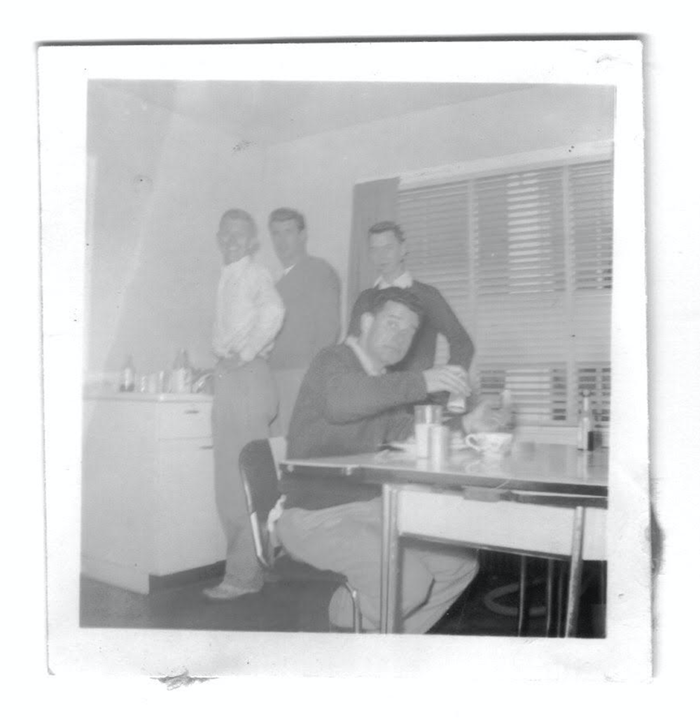 "Charlie Bashara enjoying a ""home cooked"" meal at Deek's house on N. Main Street. Brothers Frank Jordan, Tom Richards, and Pete _____ in background."