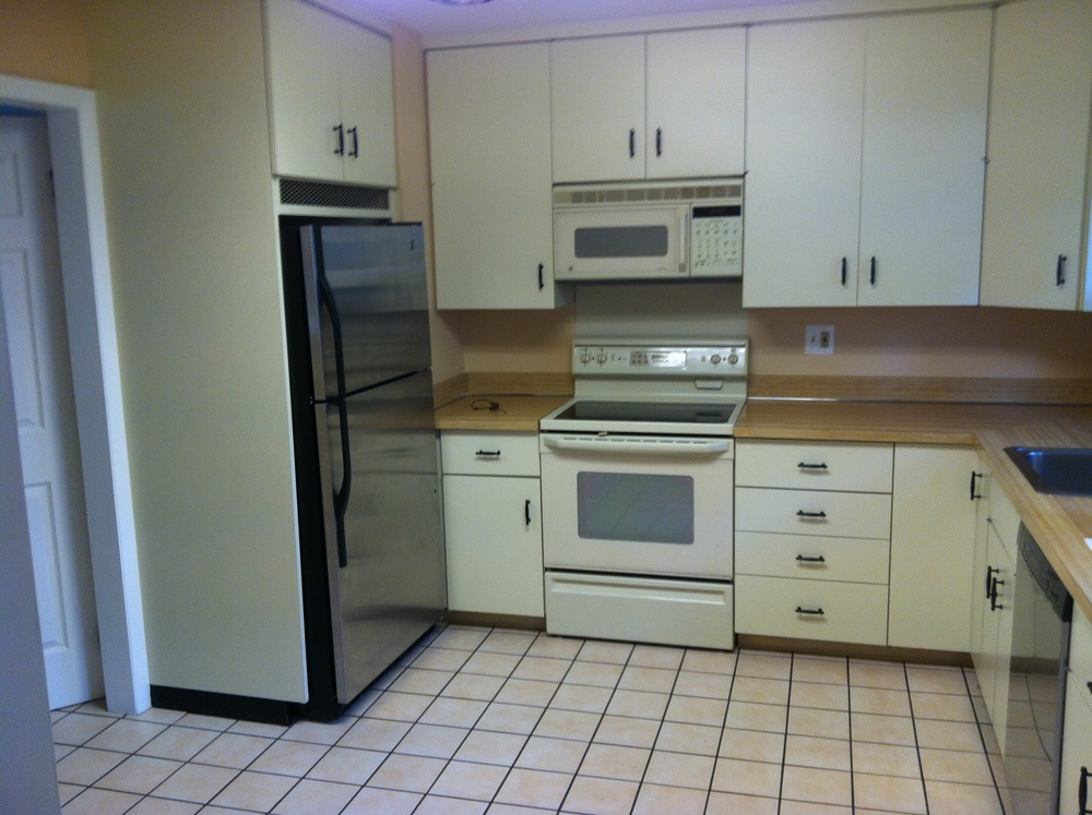 Here is our kitchen when we first moved in. Shortly after, I convinced my husband that we should refinish our wood floors and add hardwoods in the kitchen so we could have better flow.