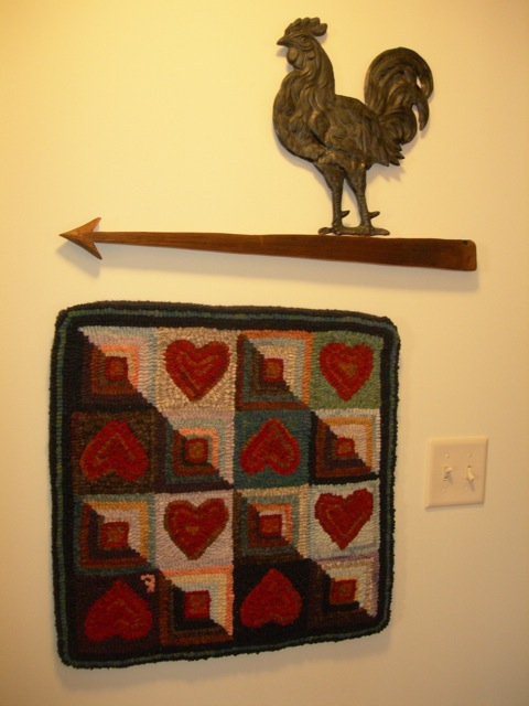 A small quilt design hooked wall hanging.
