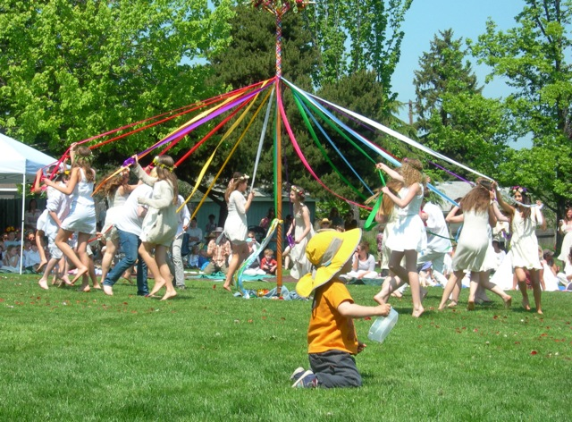 The weaving of the May pole on a bright sunny day.