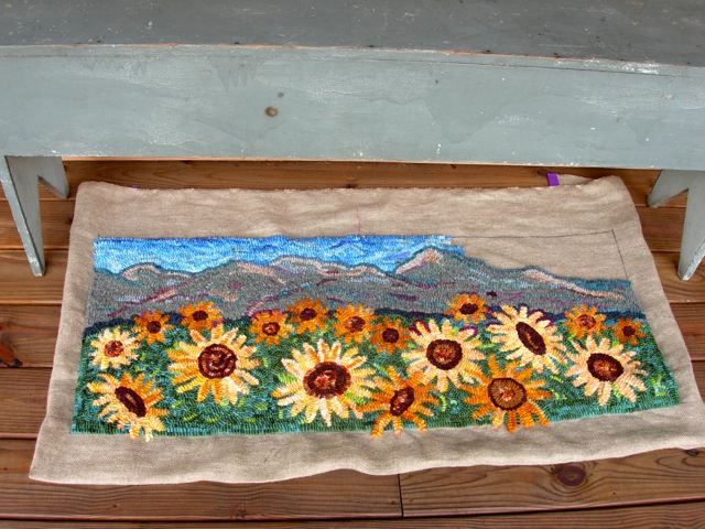 The color of the back porch bench is similar to the mountain range.
