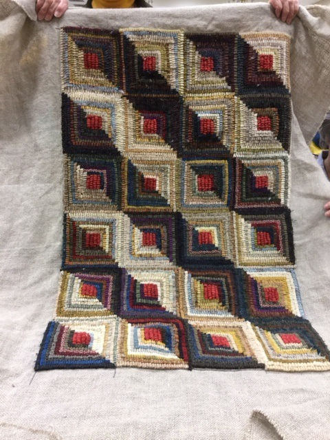 Lin Keller, a quilter and rug hooker, finished her log cabin design rug. Isn't it gorgeous?  It looks like sunlight is streaming across it.