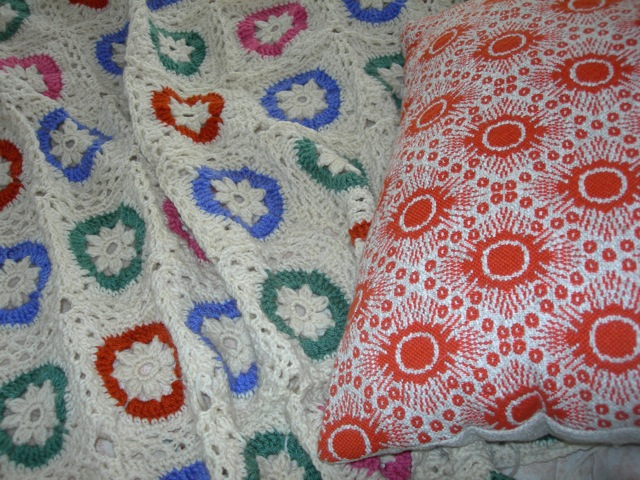 My afghan in progress on the left and a pillow from Family Heirloom Weavers on the right.  They had added a more contemporary line of designs and I couldn't resist this pillow in orange.  I'm sorry they are no longer in business.