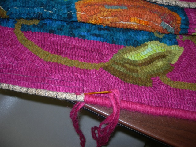 My favorite way to bind a rug. Roll linen over cotton clothesline, baste in place, and whip with yarn.