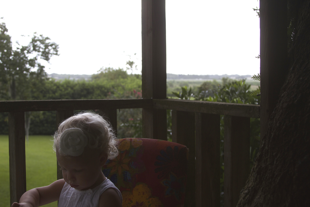Maggie at 19 months, sitting in my grandmother's chair, in the tree house, in the rain.
