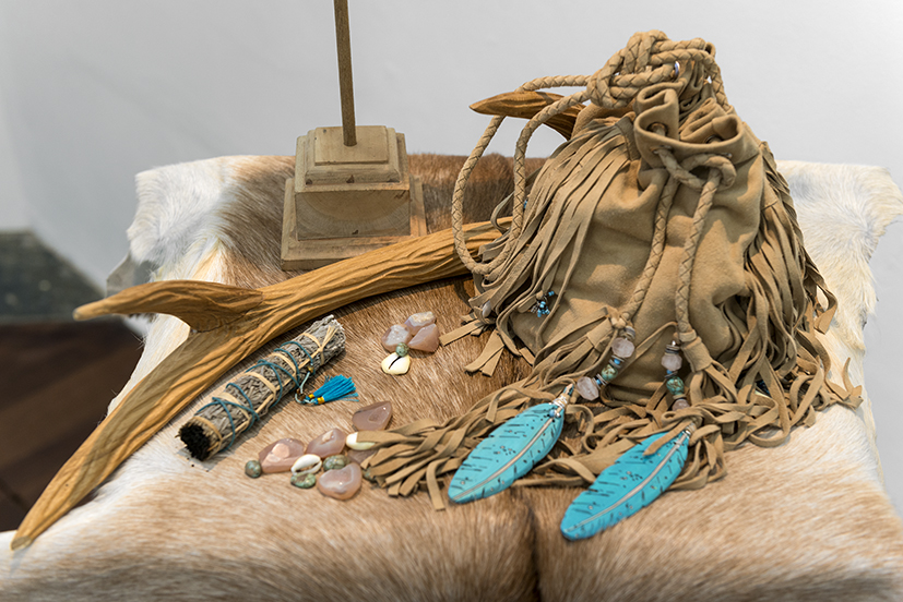29. Sarah Zel Chescoe,  Medicine Woman , 2018, repurposed suede shawl, components and findings from the artist's studio collection, turquoise, rose quartz, druzy quartz, cowrie shells, mother of pearl shell, glass beads, sage stick, ply, hand-carved teak, wire, goat hide, bone, birds nest. $1,250.