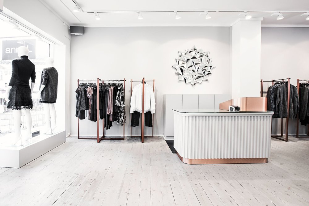 Ann-L in Holbæk, Denmark. White elements dominate the interior design and personal space around the shop allows the customer to breathe and enhance his shopping experience.
