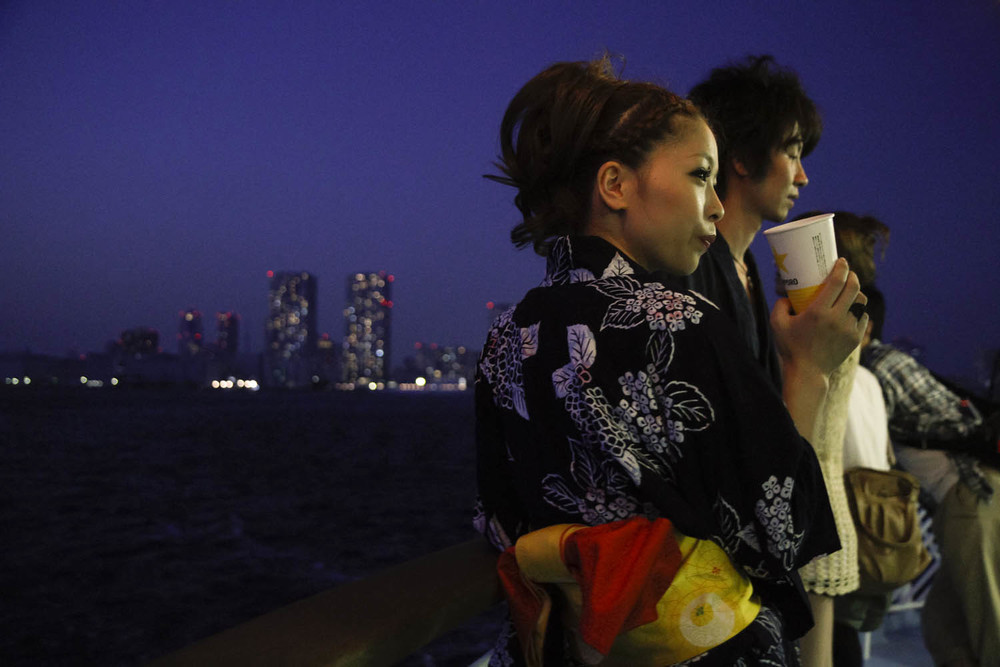 A woman wearing traditional Japanese yukata enjoys the atmosphere of the boat cruise on the Tokyo Bay. People were encouraged to wear traditional dress on the two-hour cruise.