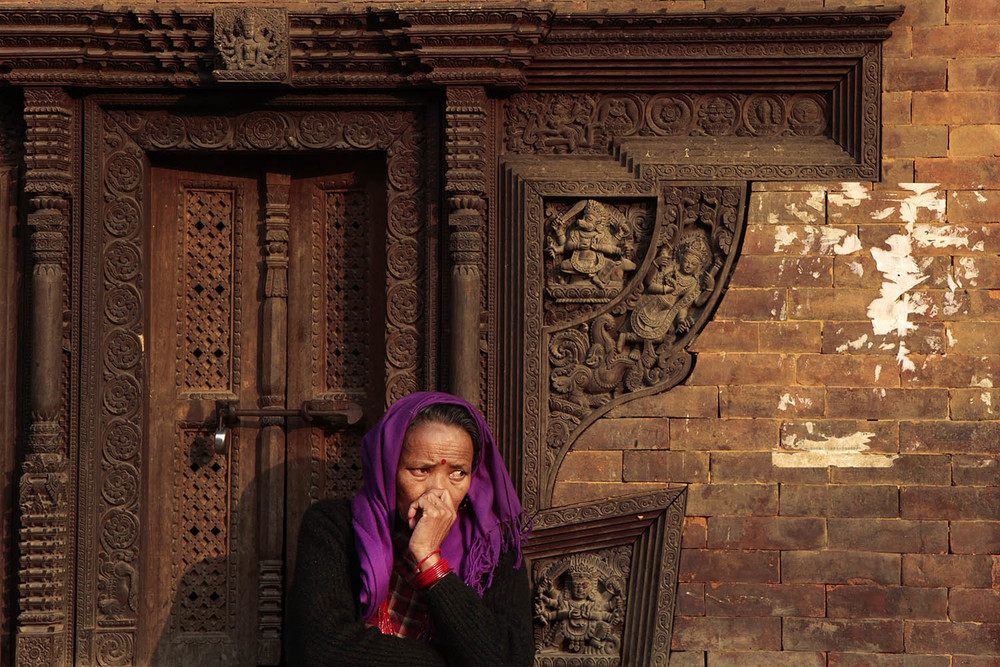 A woman sits near an ancient building in Kathmandu Durbar Square in Nepal.